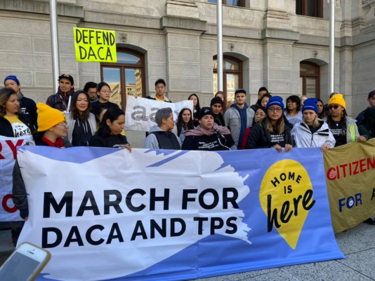 """Group of people holding banner saying """"March for DACA and TPS"""""""